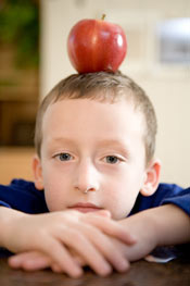 boy balancing apple on head